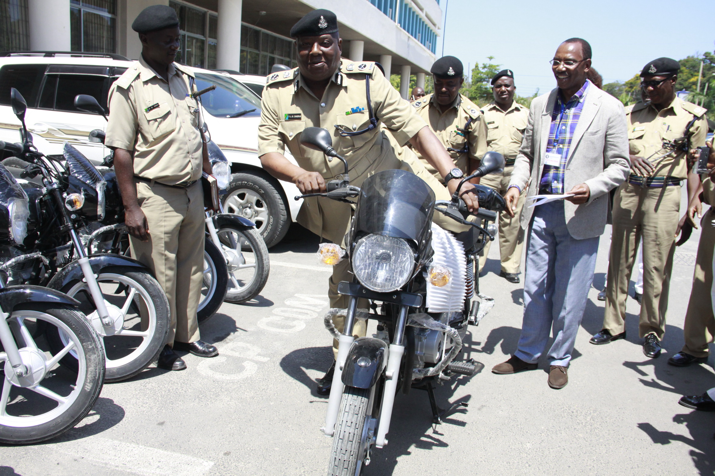Humphrey Kariuki (Chairman) hands over a motorbike to security officers in Tanzania.
